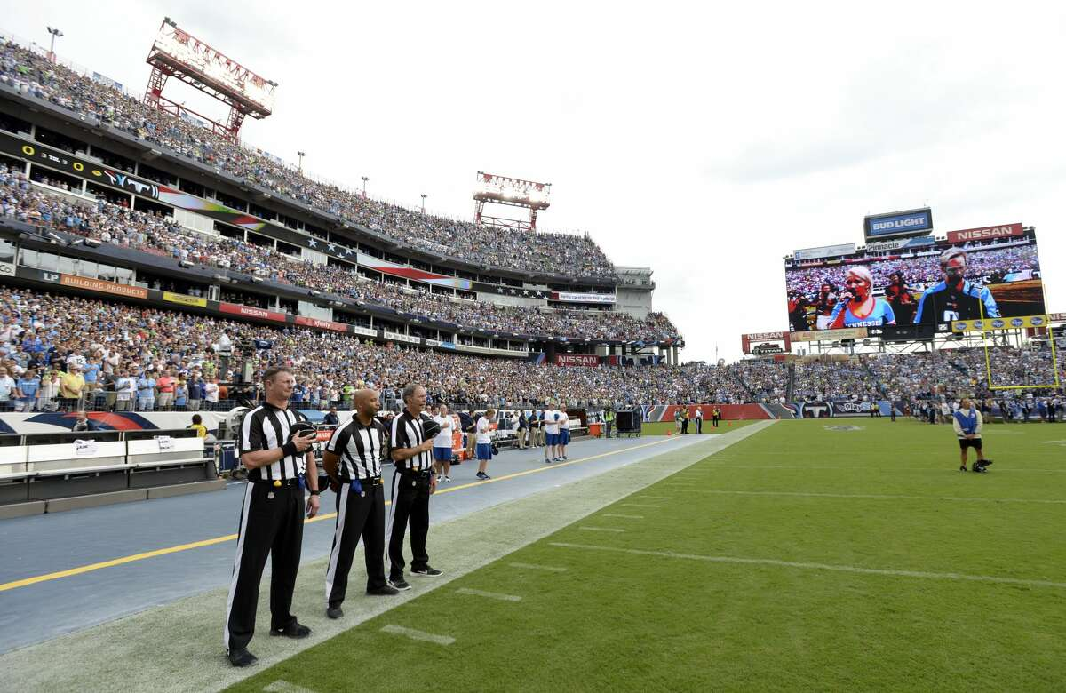 Officials stand on the sideline of the Seattle Seahawks during the playing of the national anthem before an NFL football game between the Seahawks and the Tennessee Titans Sunday, Sept. 24, 2017, in Nashville, Tenn. Neither team came out onto the field for the anthem. (AP Photo/Mark Zaleski)