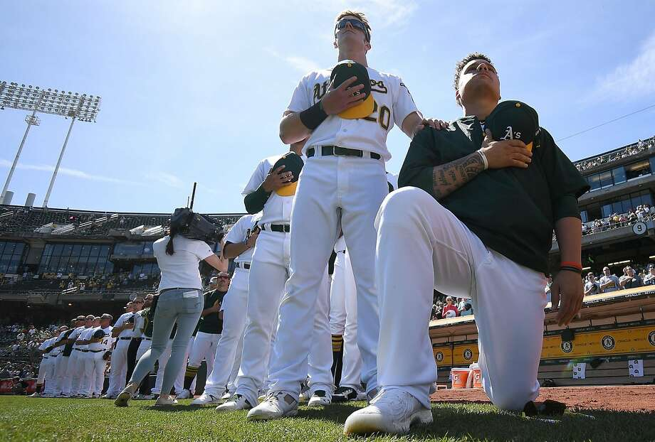 OAKLAND, CA - SEPTEMBER 24:  Bruce Maxwell #13 of the Oakland Athletics kneels in protest next to teammate Mark Canha #20 duing the singing of the National Anthem prior to the start of the game against the Texas Rangers at Oakland Alameda Coliseum on September 24, 2017 in Oakland, California.  (Photo by Thearon W. Henderson/Getty Images) Photo: Thearon W. Henderson, Getty Images