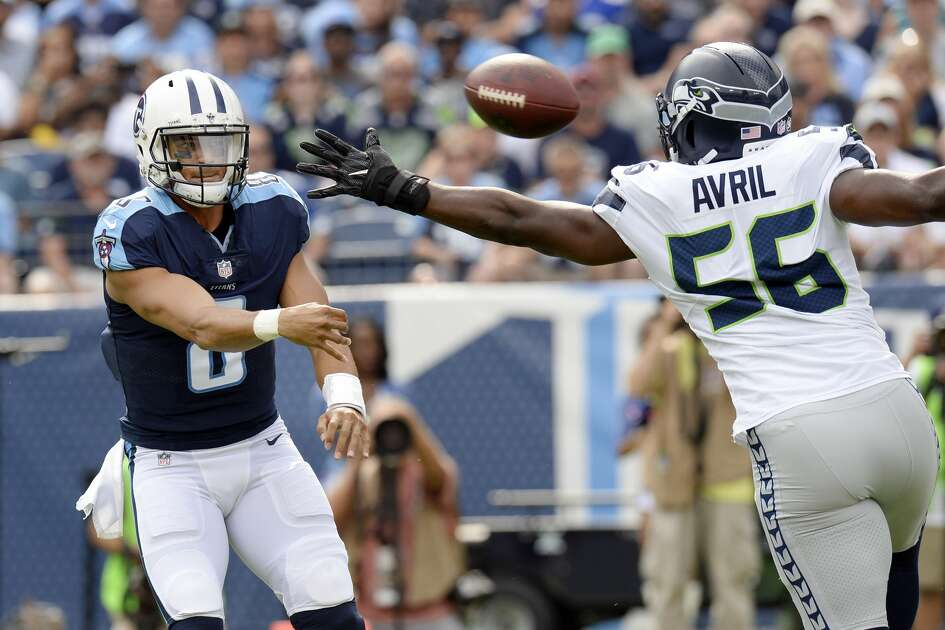 Tennessee Titans quarterback Marcus Mariota (8) passes past Seattle Seahawks defensive end Cliff Avril (56) in the first half of an NFL football game, Sunday, Sept. 24, 2017, in Nashville, Tenn. (AP Photo/Mark Zaleski)