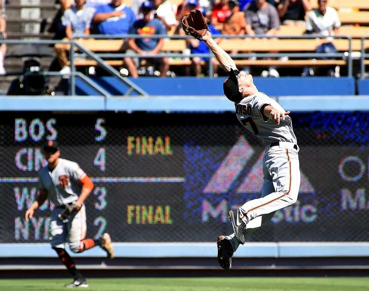 LOS ANGELES, CA - SEPTEMBER 24:  Kelby Tomlinson #37 of the San Francisco Giants leaps as a single by Curtis Granderson #6 of the Los Angeles Dodgers goes to the outfield in the first inning of the game at Dodger Stadium on September 24, 2017 in Los Angeles, California.  (Photo by Jayne Kamin-Oncea/Getty Images)