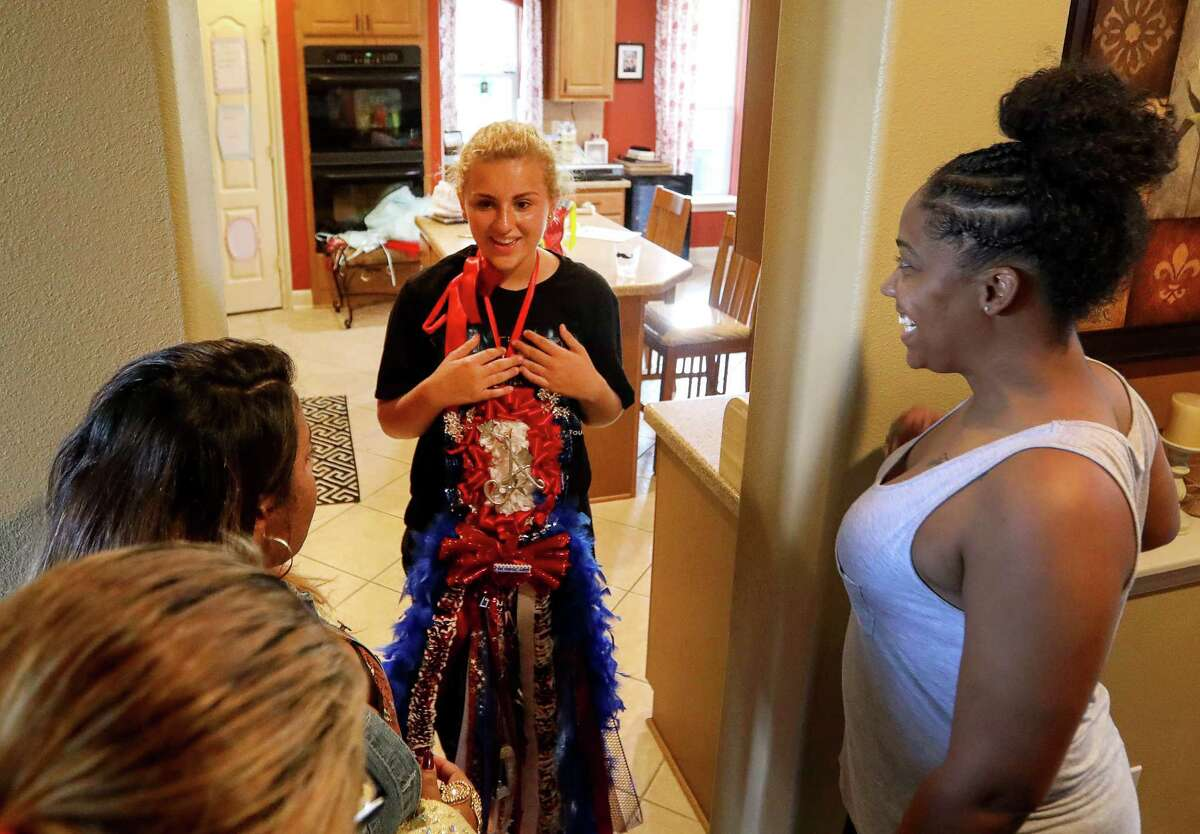 """Ashley Reel, 14, center, explains a homecoming mum to Ronisha Banks, right, Rosenda Cuevas, left, and her daughter Janiyah Tells, 16, second from left, Sunday, Sept. 24, 2017, in Spring. Banks, Cuevas and Tells are from Indiana and had not seen mums before. """"But what do they do with them?"""" Cuevas asked."""