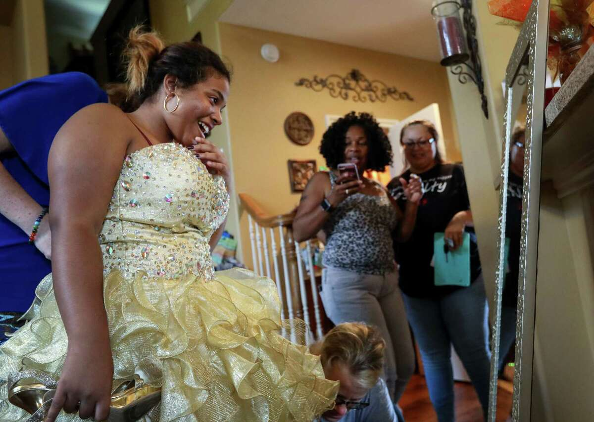 """Janiyah Tells, 16, second from left, watches as Tammy Reel, center, and Laura Clements, left, help her with her dress and shoes, as her mother Rosenda Cuevas, right, and her friend Shyra Moody, second from right, look on, at Reel's house, Sunday, Sept. 24, 2017, in Spring. """"She didn't want to tell me she wanted to go to homecoming,"""" Cuevas said. """"She didn't want to be a burden."""" Reel's daughter Ashley collected almost 2,000 homecoming dresses to distribute to victims of Hurricane Harvey."""