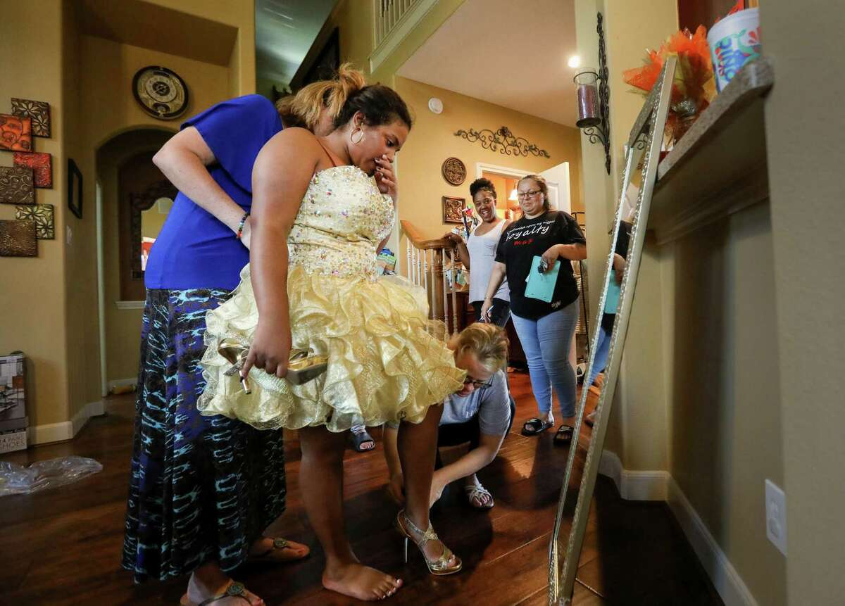"""Janiyah Tells, 16, second from left, watches as Tammy Reel, center, and Laura Clements, left, help her with her dress and shoes, as her mother Rosenda Cuevas, right, and her friend Ronisha Banks, second from right, look on, at Reel's house, Sunday, Sept. 24, 2017, in Spring. """"She didn't want to tell me she wanted to go to homecoming,"""" Cuevas said. """"She didn't want to be a burden."""" Reel's daughter Ashley collected almost 2,000 homecoming dresses to distribute to victims of Hurricane Harvey."""