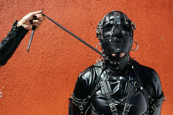 Marie Champagne holds Jason Basciano on a leash during the Folsom Street Fair in San Francisco, Calif. Sunday, September 24, 2017.