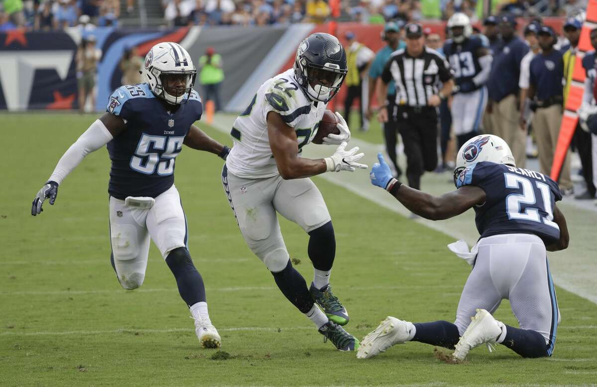 Seattle Seahawks running back C.J. Prosise (22) runs past Tennessee Titans defenders Jayon Brown (55) and Da'Norris Searcy (21) in the first half of an NFL football game Sunday, Sept. 24, 2017, in Nashville, Tenn. (AP Photo/James Kenney)