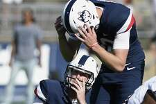 UConn kicker Michael Tarbutt, top, and holder Brett Graham react after Tarbutt missed a 35-yard field goal in the final seconds against East Carolina on Sunday.