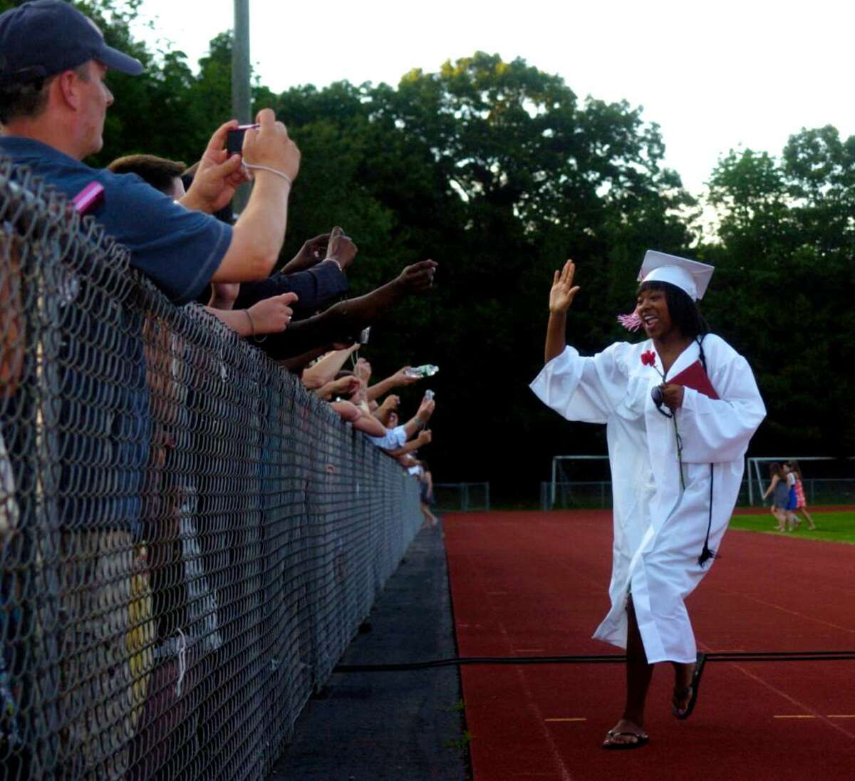 Antoinette Kinard gets a high-five from the crowd after graduating from Masuk High School during a ceremony at the school Wednesday, June 23, 2010.