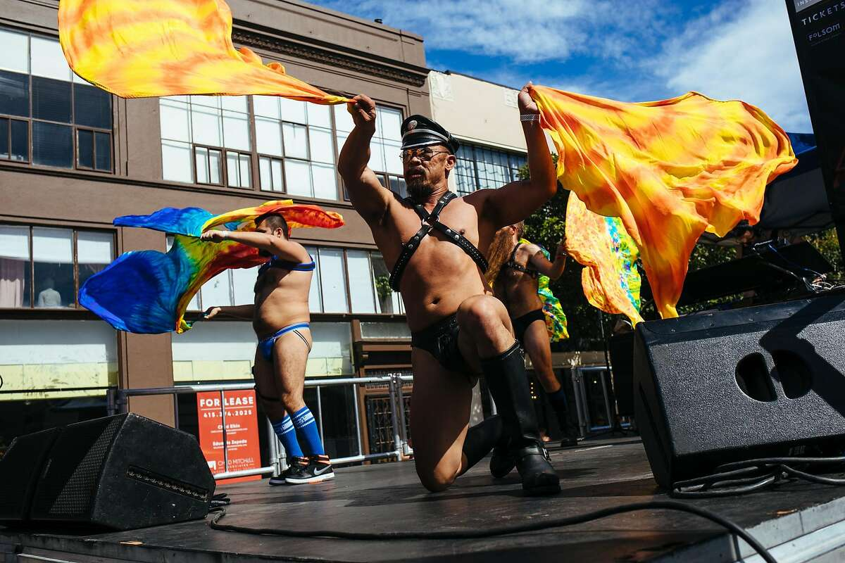 Men flag on stage during the Folsom Street Fair in San Francisco, Calif. Sunday, September 24, 2017.
