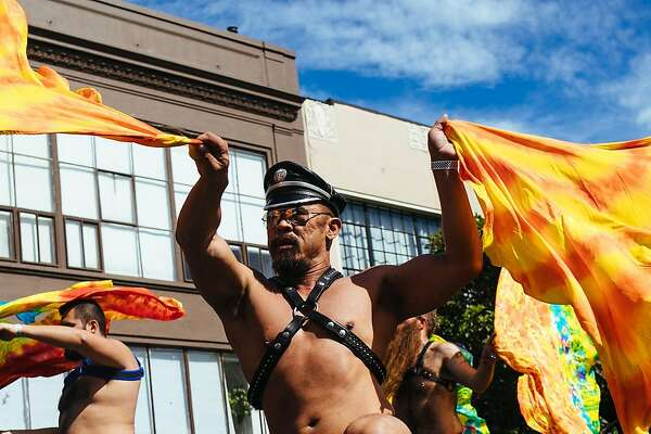 Men flag on stage during the Folsom Street Fair in San Francisco, Calif. Sunday, September 24, 2017.