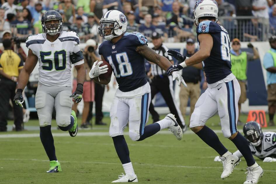 Tennessee Titans wide receiver Rishard Matthews (18) scores a touchdown on a 55-yard pass ahead of Seattle Seahawks outside linebacker K.J. Wright (50) in the second half of an NFL football game Sunday, Sept. 24, 2017, in Nashville, Tenn. (AP Photo/James Kenney)