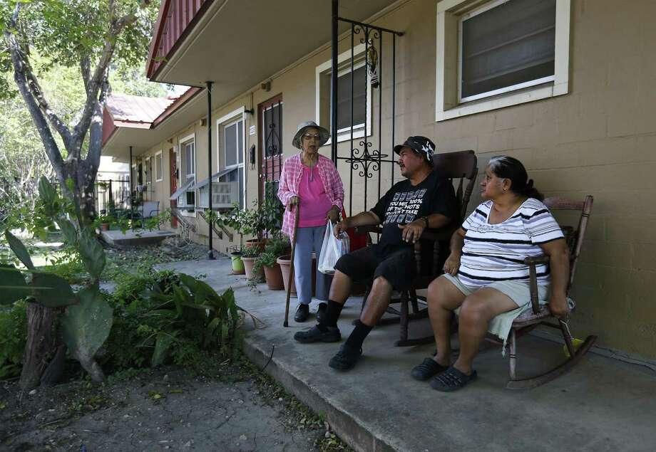 Petra de la Rosa (from right) and her nephew, Roque Resendez, chat with neighbor Maria de la Cruz, at their Alazan Courts apartments complex on Friday, Sept. 8, 2017. The San Antonio Housing Authority will seek another federal Choice Neighborhood grant with plans to potentially tear down and redevelop the property. The grant funds, if awarded, would also support the transformation of the surrounding neighborhood. SAHA is hoping to replicate the success it had on the East Side when it tore down the Wheatley Courts public housing project and built the new mixed-income East Meadows apartment complex in its place. (Kin Man Hui/San Antonio Express-News) Photo: Kin Man Hui, Staff / San Antonio Express-News / ©2017 San Antonio Express-News