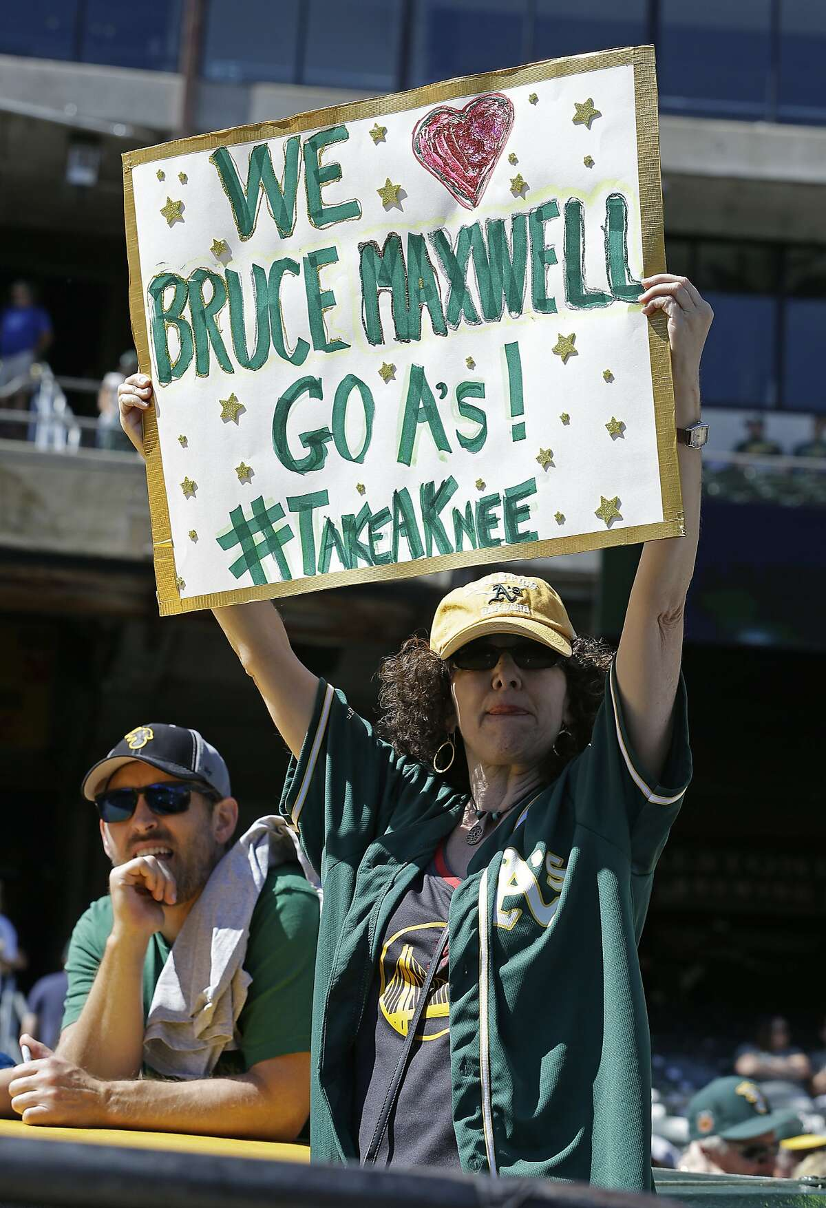 Nancy Levine of Marin, Calif., holds a sign in support of Oakland Athletics' Bruce Maxwell, who knelt during the national anthem for a second day prior to the baseball game against the Texas Rangers Sunday, Sept. 24, 2017, in Oakland, Calif. (AP Photo/Ben Margot)
