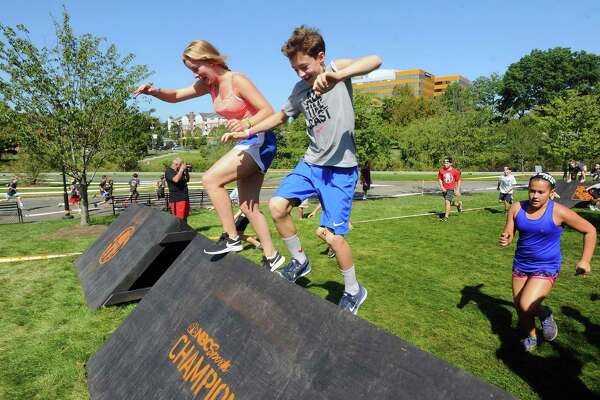12-year-old Arthur Devillers, center, of Darien, and 18-year-old Valentine Lassarat of France climb over an obstacle together during the Spartan Kids Race at Mill River Park in downtown Stamford on Sunday.