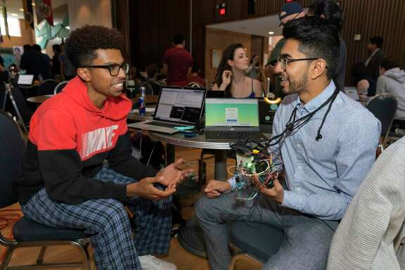 Ammar Al-kahfah (left) talks with Harsh Patel (right) about their Memoreyes facial recognition device during HackRice, Rice University's annual hackathron event on Sunday.