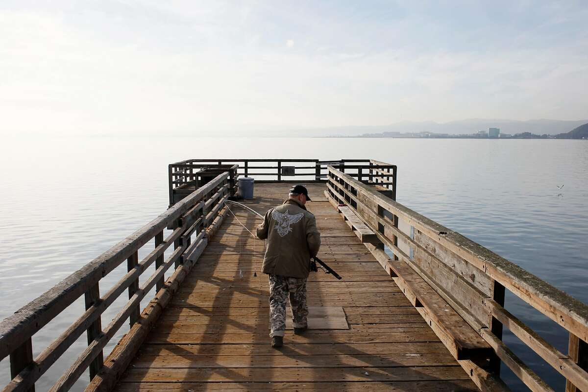 Minh, who didn't want his last name used, prepares to set up a fishing rod at the ned of a pier at Candlestick Point State Recreation Area on January 21, 2014 in San Francisco, Calif. Nearby, a derelict boat lies partially submerged. Officials said the boat has been there for about a month and that removing the wreck is a difficult proposition involving numerous jurisdictions.