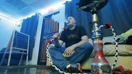 Hookah Harem owner Darin Ungerman smokes Thursday Sept. 21 at Hookah Harem.