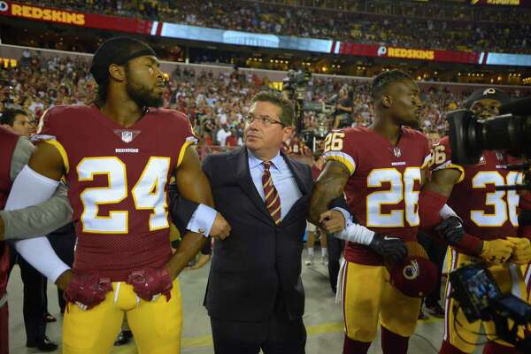 Redskins owner Daniel Snyder links arms with cornerbacks Josh Norman, left, and Bashaud Breeland during the national anthem Sunday night.