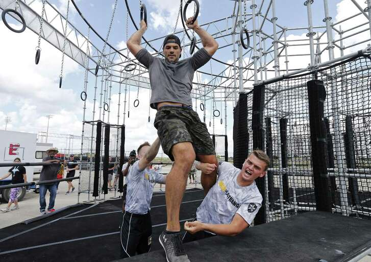 Pfc. Jayme Patterson (left) and Spc. Bryce Forseth help coach Wes Okerson of Team Baker from Camp Humphreys in South Korea finish an obstacle in the BOSS Strong Championship.