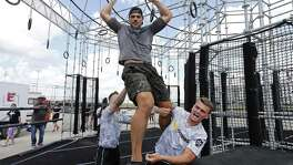 Team Baker, from Camp Humphreys in South Korea,  Pfc. Jayme Patterson (left) and Spc. Bryce Forseth (right) help coach Wes Okerson finish an obstacle on the BOSS Strong Championship obstacle course Sunday Sept. 24, 2017 at Retama Park.