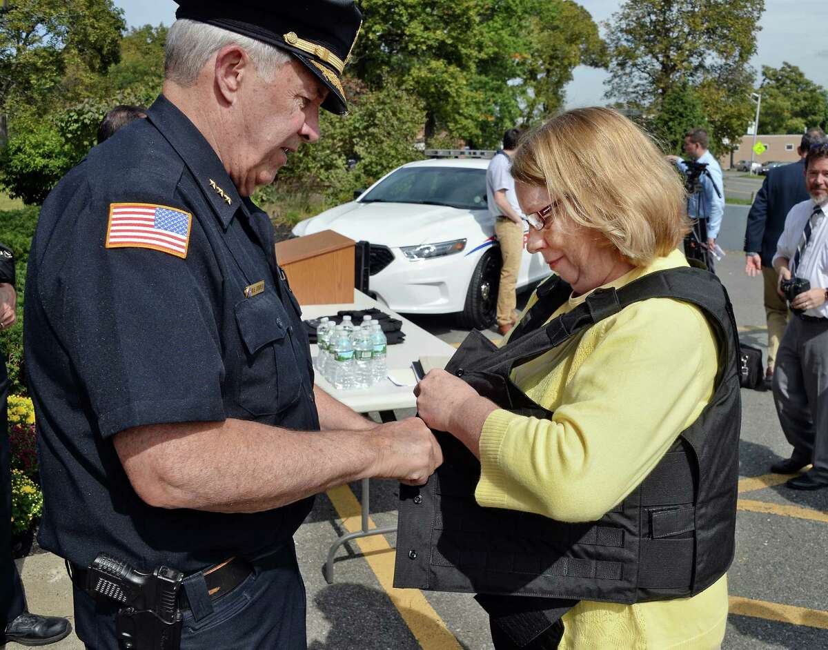 Menands Police Chief Michael O'Brien, left, has Mayor Megan Grenier try on a new bulletproof vests, part of a PERMA pilot program, during a news conference Thursday Sept. 21, 2017 in Menands, NY. (John Carl D'Annibale / Times Union)