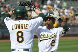 OAKLAND, CA - SEPTEMBER 24:  Khris Davis #2 of the Oakland Athletics is congratulated by Jed Lowrie #8 after Davis hit a two-run homer against the Texas Rangers in the bottom of the fifth inning at Oakland Alameda Coliseum on September 24, 2017 in Oakland, California.  (Photo by Thearon W. Henderson/Getty Images)