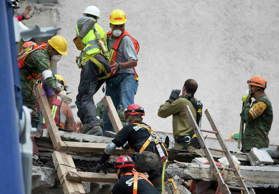 Rescue workers quickly evacuate the site of a felled office building brought down by a 7.1-magnitude earthquake, in the Roma Norte neighborhood of Mexico City, Sunday, Sept. 24, 2017. As rescue operations stretched into day 6, residents throughout the capital have held out hope that dozens still missing might be found alive. (AP Photo/Moises Castillo) Photo: Moises Castillo, STF / Copyright 2017 The Associated Press. All rights reserved.
