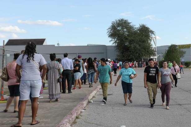 Harris County Hurricane Harvey victims line up outside the entrance at Greenspoint Mall to receive the Disaster Supplemental Nutrition Assistance Program distributed from Texas Health and Human Services Sunday.