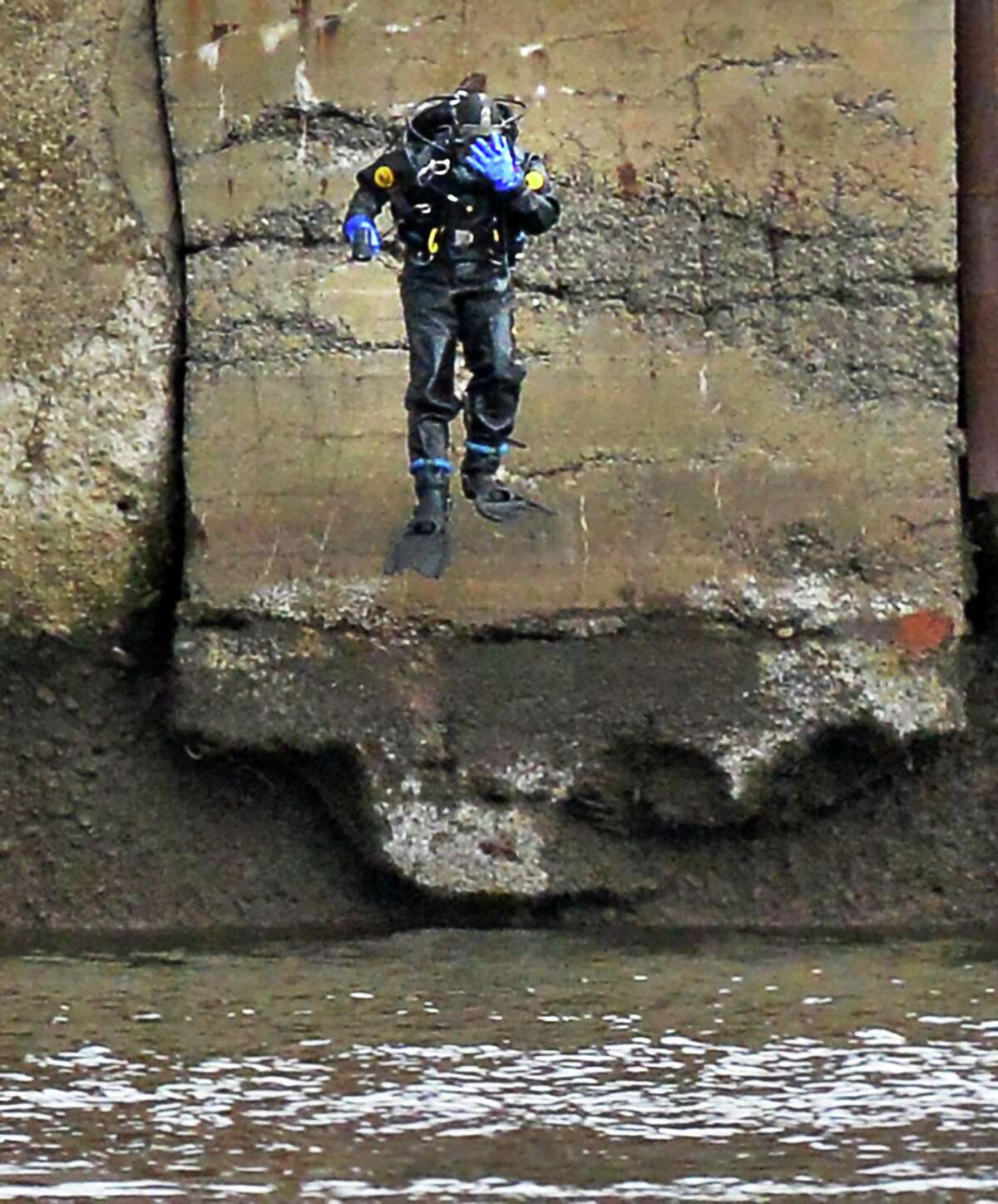 A state police diver jumps into th Hudson River as the search continues for Noel Alkaramla below the John P. Taylor Apartments Tuesday Dec. 15, 2015 in Troy, NY. (John Carl D'Annibale / Times Union)