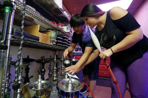 Hookah Harem general manager Se Yun Chong (left) and  assistant Courtney Gonzales prepare hookahs.
