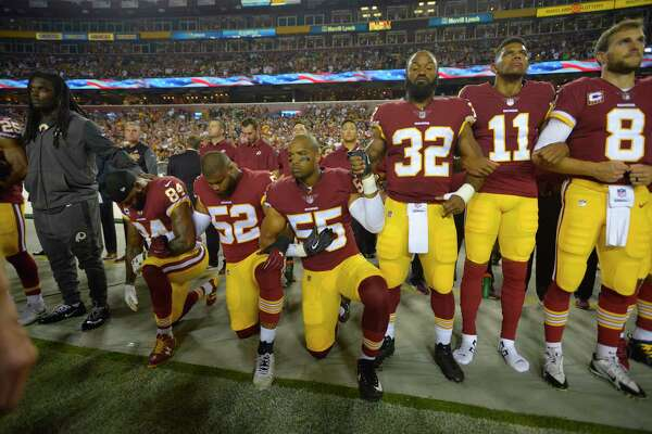 Redskins players during the national anthem Sunday night at FedEx Field in Landover, Md.