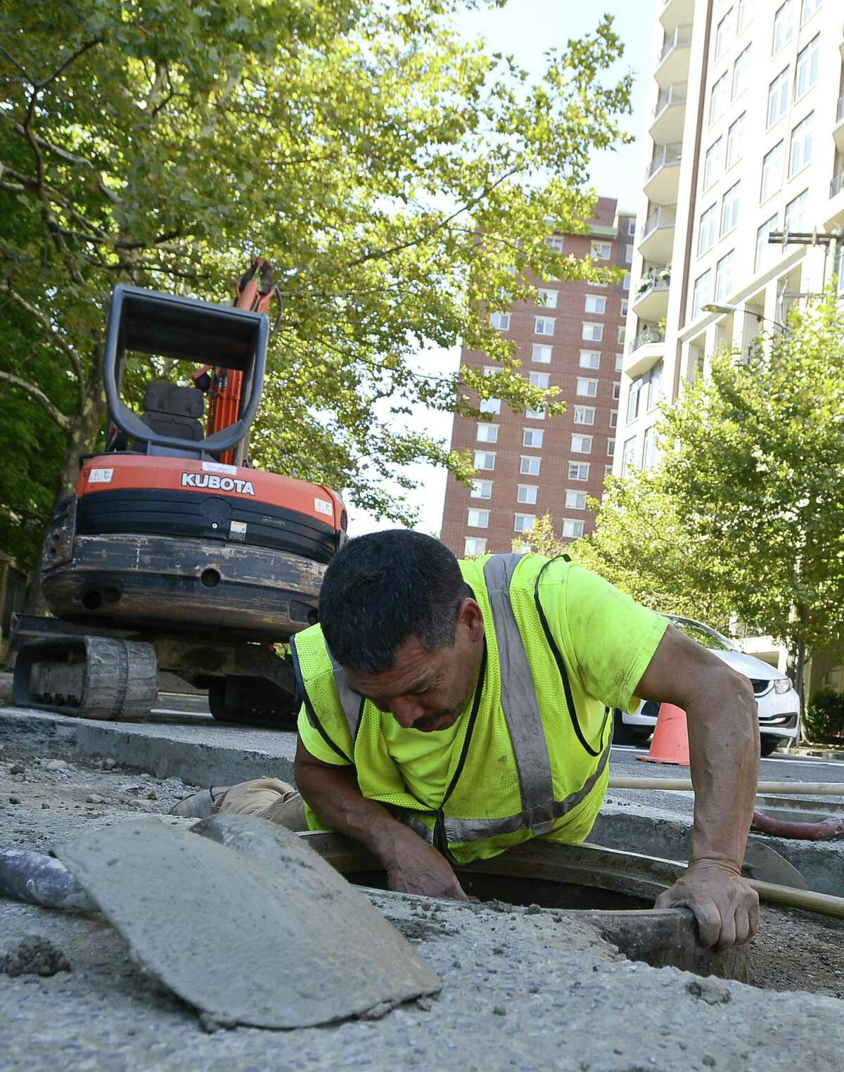"""Martin Farias of Grasso Companies, Norwalk, CT, finishes repairs to a 12"""" storm drain at the corner of Forest and Grove Street in Stamford, Connecticut on Friday, Sept. 22, 2017. The work was being done in preparation for paving of Forest Street next week."""