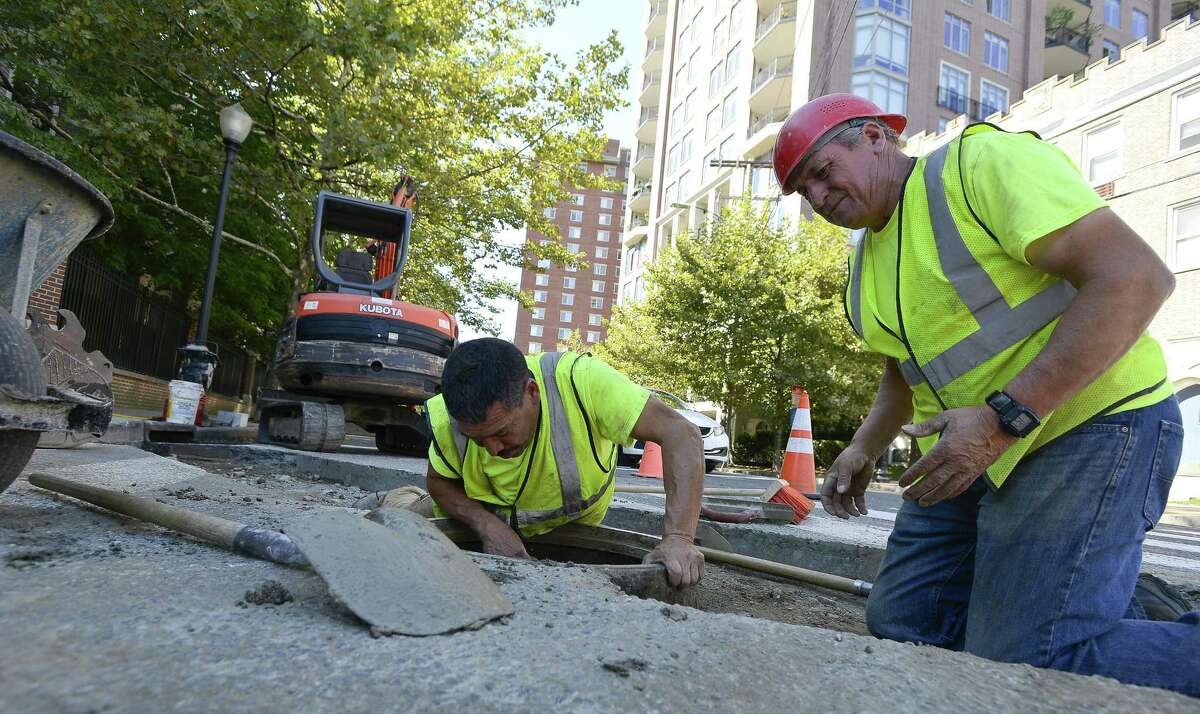 Martin Farias and Domingos Daerira, of Grasso Companies, finish repairs to a storm drain at the corner of Forest and Grove streets before the roadway is paved.