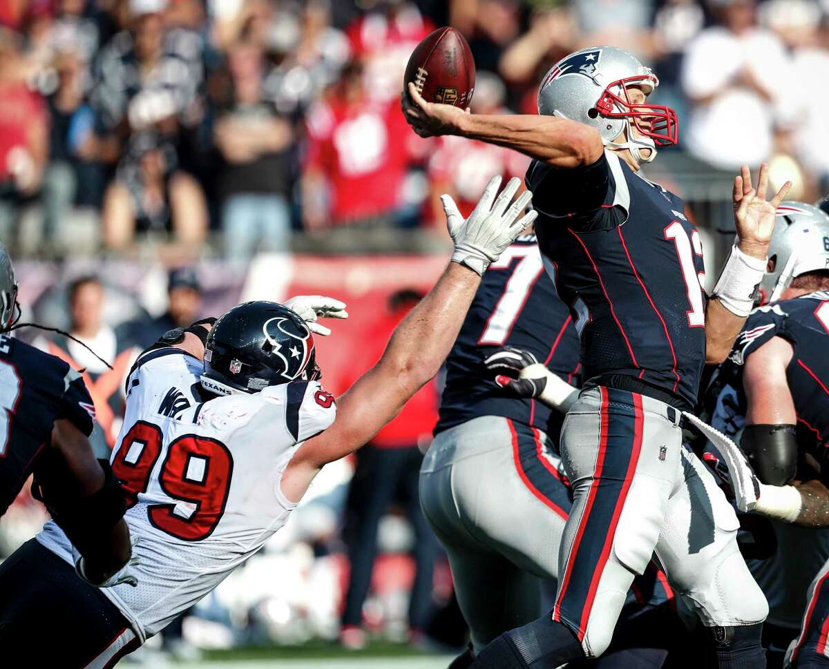 Houston Texans defensive end J.J. Watt (99) reaches out in vain to stop New England Patriots quarterback Tom Brady (12), as he throws a 25-yard touchdown pass to wide receiver Brandin Cooks during the fourth quarter of an NFL football game at Gillette Stadium on Sunday, Sept. 24, 2017, in Foxbourough, Mass. ( Brett Coomer / Houston Chronicle )