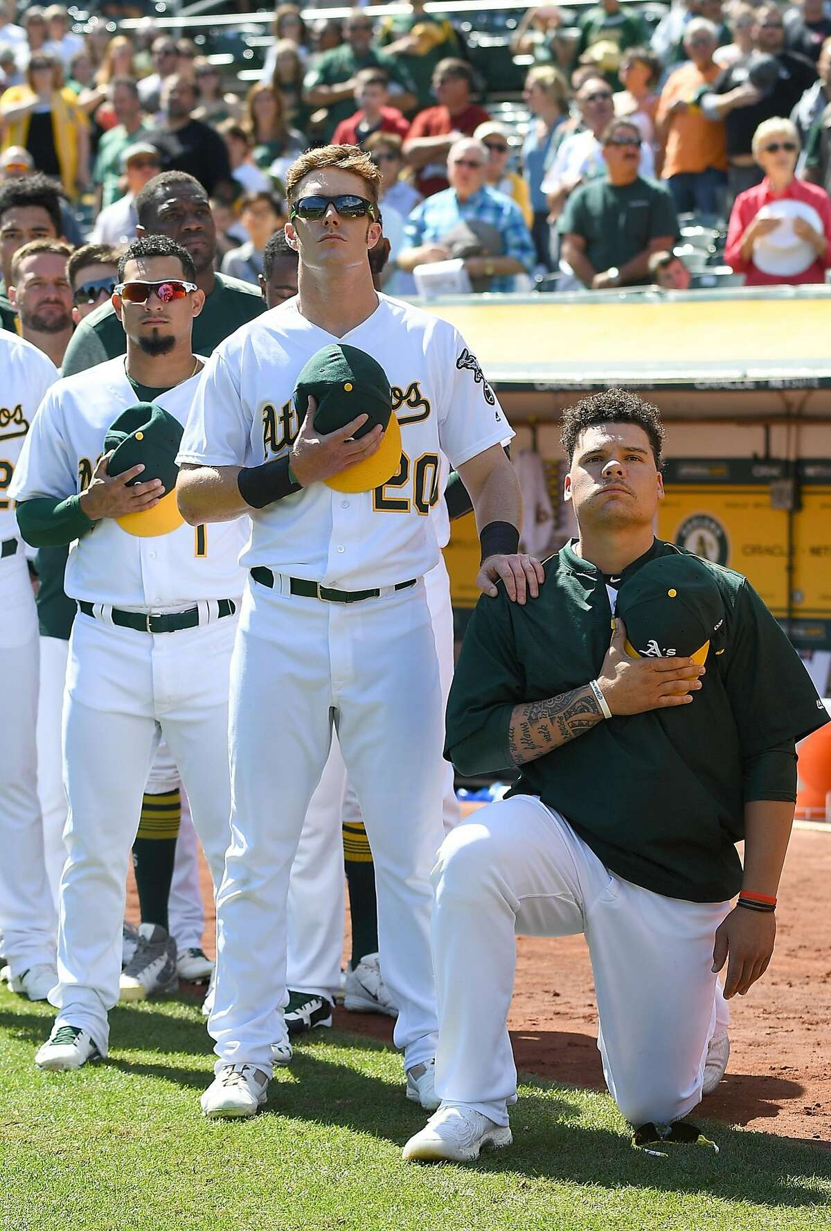 Bruce Maxwell of the Oakland Athletics kneels in protest next to teammate Mark Canha #20 duing the singing of the National Anthem prior to the start of the game against the Texas Rangers at Oakland Alameda Coliseum on September 24, 2017 in Oakland, California.