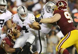 LANDOVER, MD - SEPTEMBER 24: Quarterback Derek Carr #4 of the Oakland Raiders is taken down by tight end Vernon Davis #85 of the Washington Redskins in the third quarter at FedExField on September 4, 2017 in Landover, Maryland.  (Photo by Patrick Smith/Getty Images)