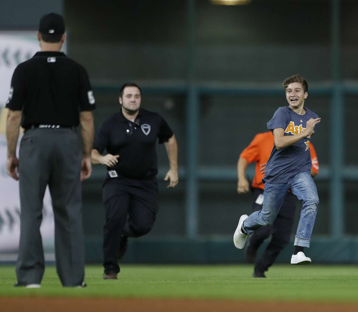 A kid runs around the field as security and police gave chase during the seventh inning of an MLB baseball game at Minute Maid Park, Sunday, Sept. 24, 2017, in Houston. ( Karen Warren / Houston Chronicle )