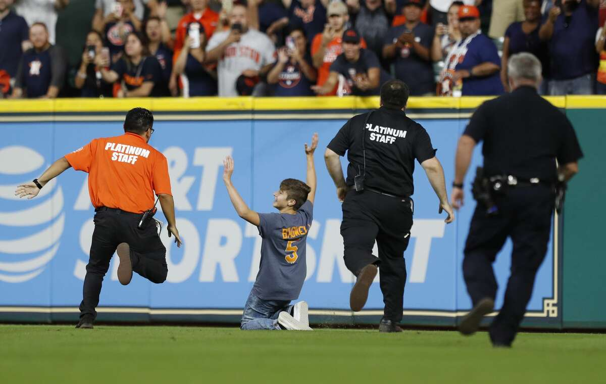 A kid stops as security and police gave chase during the seventh inning of an MLB baseball game at Minute Maid Park, Sunday, Sept. 24, 2017, in Houston. ( Karen Warren / Houston Chronicle )