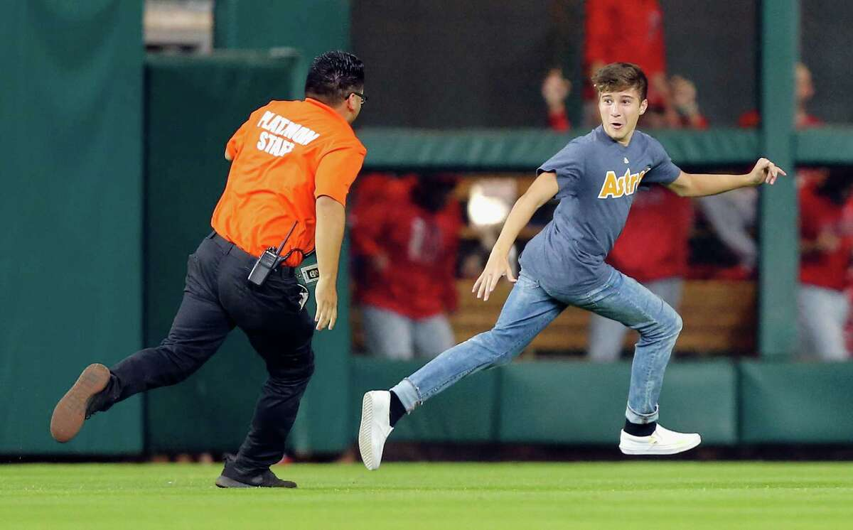 HOUSTON, TX - SEPTEMBER 24: A fan runs onto the field in the seventh inning during a baseball game between the Los Angeles Angels of Anaheim and Houston Astros at Minute Maid Park on September 24, 2017 in Houston, Texas.
