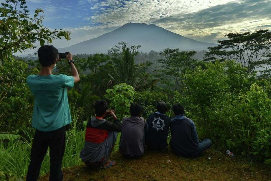 People look at Mount Agung in Karangasem on the Indonesian resort island of Bali on September 24, 2017.  Authorities have raised alert levels for a volcano on the Indonesian resort island of Bali after hundreds of small tremors stoked fears it could erupt for the first time in more than 50 years. Photo: AFP Contributor/AFP/Getty Images