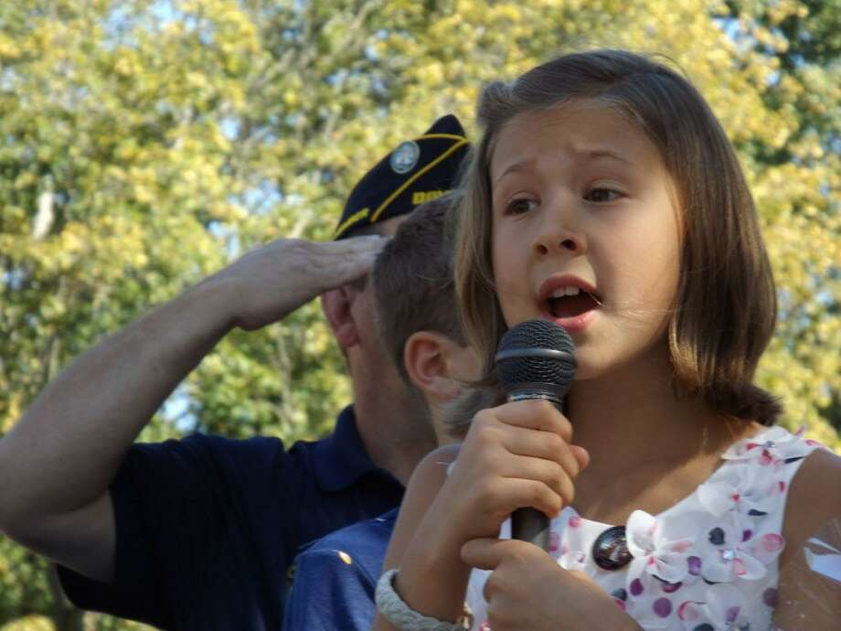 Hazel Pufahl, 8, of Ashford has been singing at memorial ceremonies in the city of Middletown. Here, she takes on the National Anthem at the unveiling of the Disabled American Veterans monument on Veteran's Green Saturday. Photo: Sloan Brewster Photo