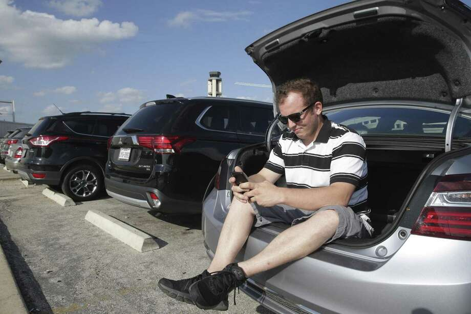 Employing a trick he learned in the Florida heat, Uber driver Michael Coon stays cool in the trunk of his car at the airport. Photo: Tom Reel /San Antonio Express-News / 2017 SAN ANTONIO EXPRESS-NEWS