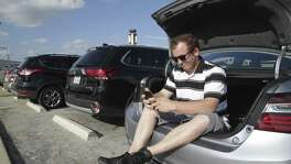 Employing a trick he learned in the Florida heat, Michael Coon stays cool in the trunk of his car rather than running the motor for air conditioning as Uber drivers gather at the airport staging area on September 22, 2017.