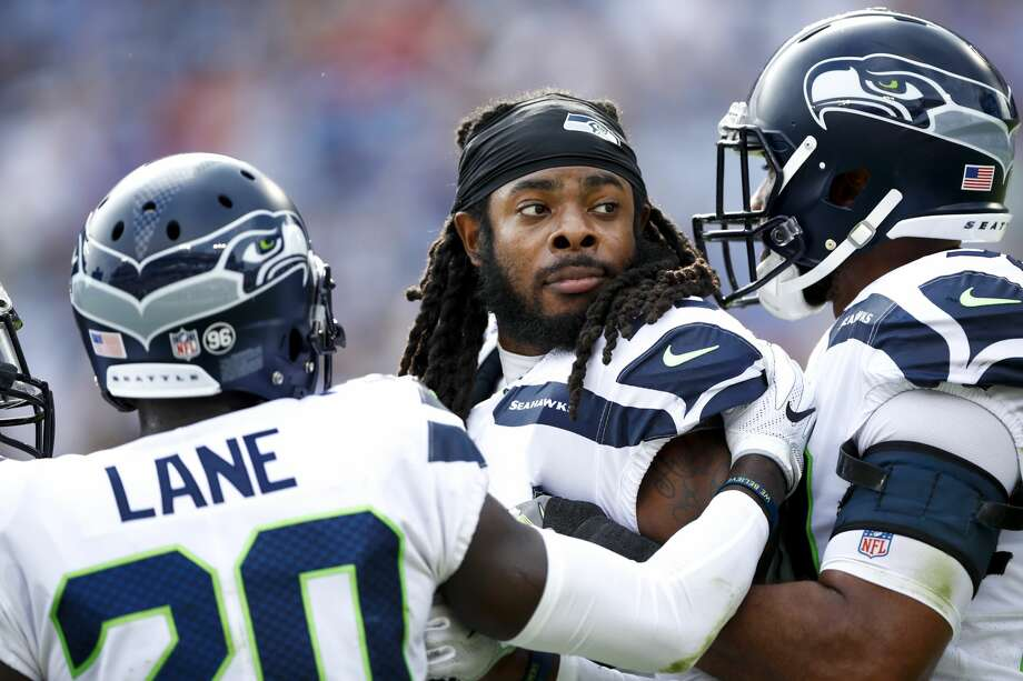 Cornerback Richard Sherman of the Seahawks is held back by his team after committing a foul against the Tennessee Titans at Nissan Stadium in Nashville last Sunday. Photo: Getty Images