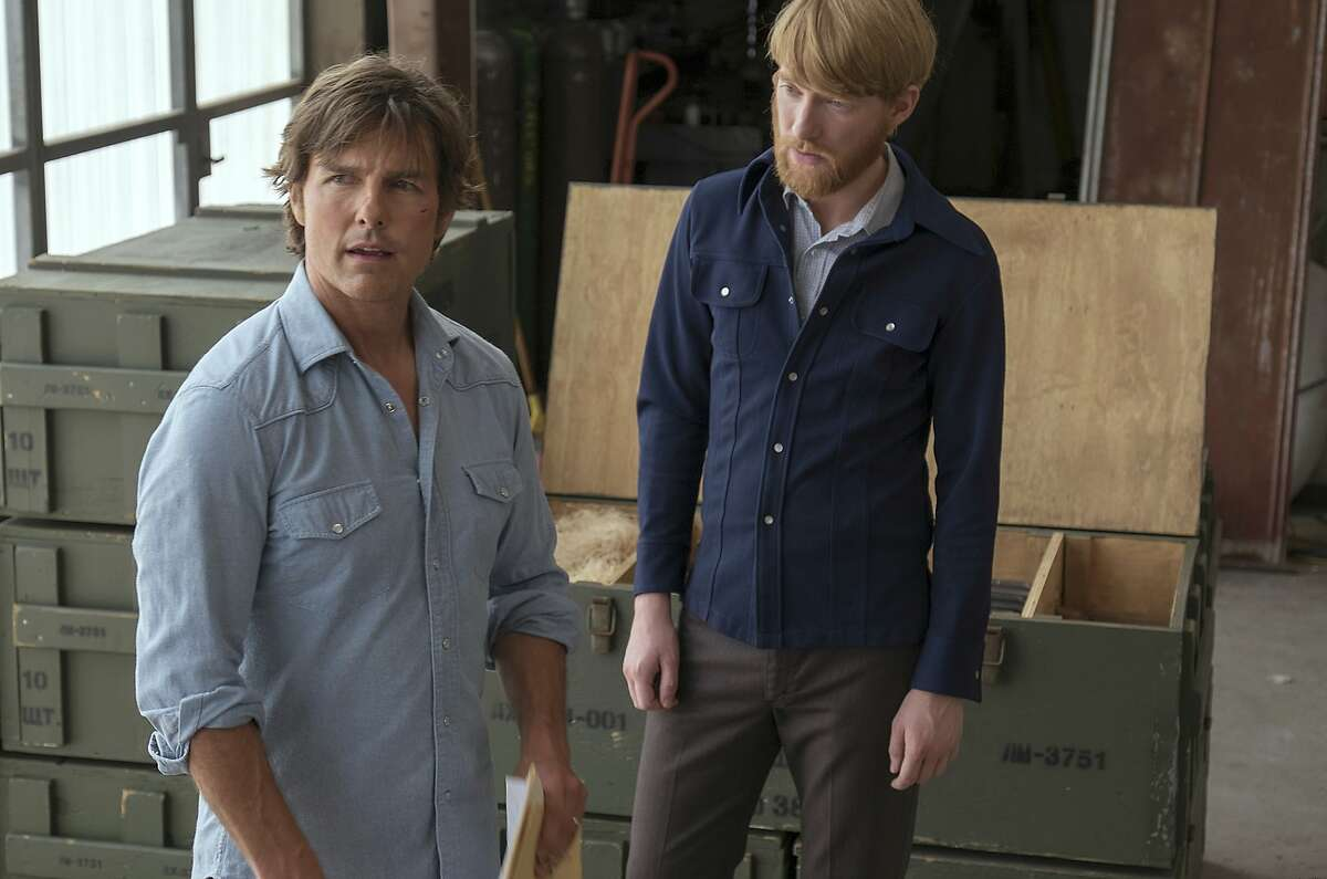 """This image released by Universal Pictures shows Tom Cruise, left, and Domhnall Gleeson in a scene from, """"American Made."""" (David James/Universal Pictures via AP)"""