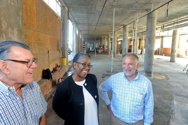 Carol Nixon, center, head of the AFL-CIO's Housing Investments Trust, stands with developers Geof Ravenstine, left, a Gary Flocco, right, at the Cherry Street Lofts project in Bridgeport, Conn. Sept. 25. 2017.
