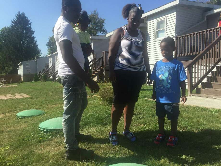 Wayne Commissiong, Lateisha Brookins and their son Jayden stand next to the septic tank pipe on Sept. 25, 2017. Jayden fell into the tank last week. Photo: Steve Hughes