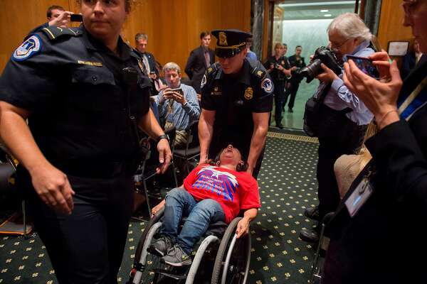 US Capitol Police remove protestors from the US Senate Committee on Finance hearing on the Graham-Cassidy-Heller-Johnson Proposal on reforming health care on Capitol Hill in Washington, DC, September 25, 2017. / AFP PHOTO / SAUL LOEBSAUL LOEB/AFP/Getty Images