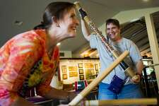"""Heather Naessens of Midland, right, dances and plays a rain stick as """"Shiny"""" from the Moana soundtrack plays from a CD player during a music jam session led by Barbara Jacques, a volunteer with Creative 360, left, on Monday, Sept. 25, 2017. The jam session is held weekly and is designed to bring individuals together to play music and develop social skills in a structured setting. (Katy Kildee/kkildee@mdn.net)"""