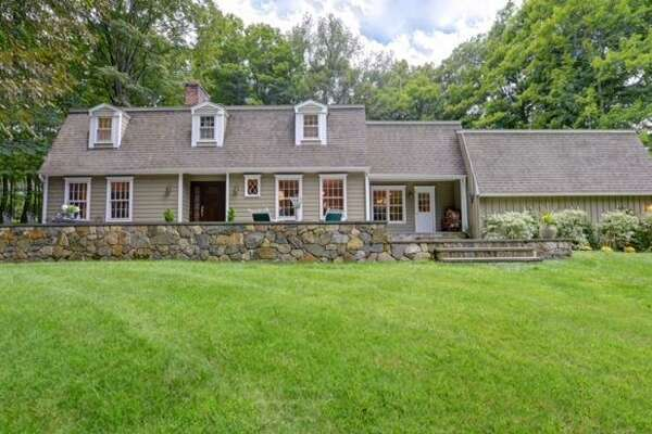 The gray custom colonial house at 17 Skunk Lane sits in a private setting yet not far from town amenities including two train stations, a farm, country club, and library.