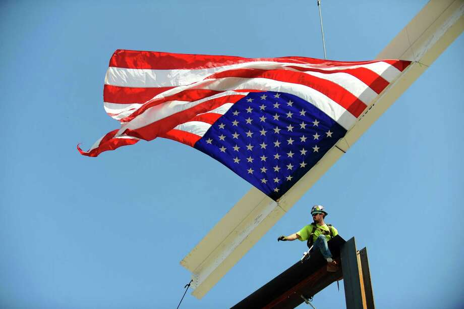 A construction worker reaches for the final steel beam before placing and securing it during the topping off ceremony for the new police station in Stamford, Conn. on Monday, Sept. 25, 2017. Photo: Michael Cummo / Hearst Connecticut Media / Stamford Advocate